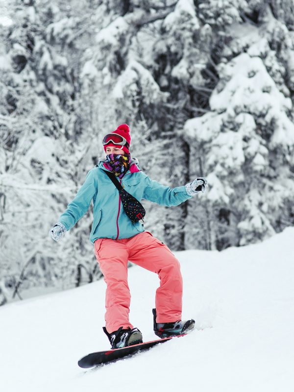 Woman in blue ski jacket and pink pants stands on the snowboard somewhere in winter forest